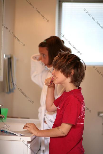 Children in a bathroom brushing hair and teeth.