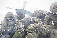 Troops huddle together over their kit as a Merlin helicopter takes off during practice in the Arctic, in the mountains near Bardufoss, Norway. <br /> <br /> In 2019 the Arctic exercise Clockwork passed 50 years of training in Norway, and now has a permanent base within the Norwegian Air Force base at Bardufoss. <br /> <br /> 845 Naval Air Squadron is a squadron of the Royal Navy's Fleet Air Arm. Part of the Commando Helicopter Force, it is a specialist amphibious unit operating the Leonardo Commando Merlin Mk3 helicopter and provides troop transport and load lifting support to 3 Commando Brigade Royal Marines.<br /> <br /> &copy;Fredrik Naumann/Felix Features