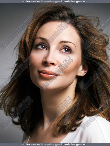 Portrait of a beautiful smiling caucasian woman with brown hair with daydreaming expression in her thirties
