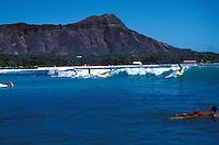 Surfing near famous Diamond head crater or Mount Leahi, Waikiki beach, Island of Oahu
