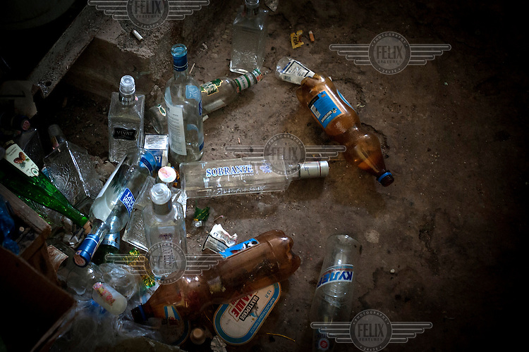Empty beer and vodka bottles left on the floor of a dormitory for workers at the relocation project for radioactive mining waste dump No.3. Some workers believe that drinking vodka helps clear the radiation from their bodies.