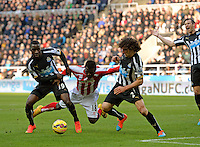 Mame Biram Diouf of Stoke City (centre) goes down after a challenge from Fabricio Coloccini of Newcastle United (right) and Massadio Haidara of Newcastle United