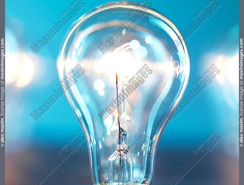 Closeup of lit up incandescent light bulb on blue background. Power consumption concept.