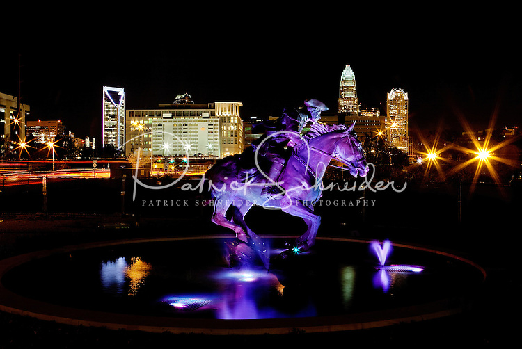 "The Captain Jack Statue ""The Spirit of Mecklenburg"" glows before the nighttime Charlotte skyline. The statue was created by The May 20th Society, an organization dedicated to the 1775 signing of the Mecklenburg Declaration of Independence. Artist Chas Fagan created the statue, which is located on the Little Sugar Creek Greenway at the corner of 4th Street and Kings Drive."