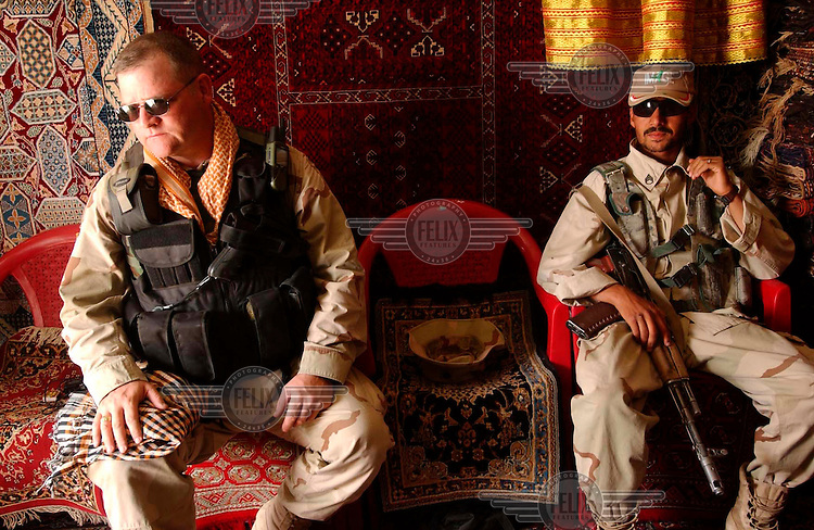 An American member of the Civil Affairs unit of the US Army, accompanied by his Afghan interpreter, shops for matching scarves at a carpet shop in Kandahar. The scarves are to be used to identify all members of a given American unit on a given day, to distinguish them from hostile elements posing as pro-Americans.