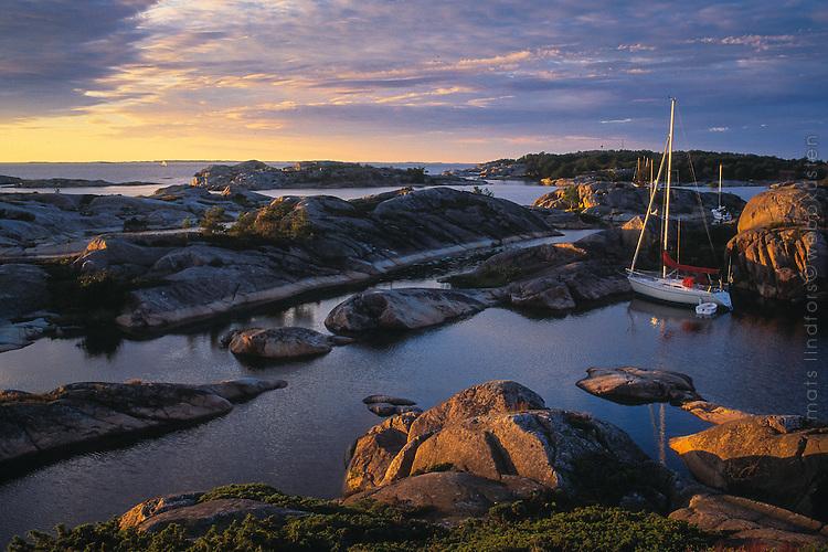 Segelbåt förtöjd i naturhamn bland skären i Stora-Nassa i Stockholms ytterskärgård. / Sailboat moored in natural harbor among the islands of Stora Nassa in Stockholm archipelago Sweden.