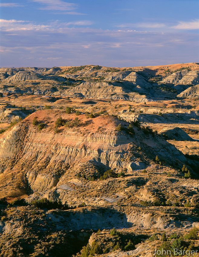 NDTR_121 - USA, North Dakota, Theodore Roosevelt National Park, Evening light defines eroded, sedimentary hills and grassy plains in autumn, Painted Canyon Overlook, South Unit.