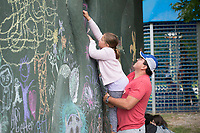 NWA Democrat-Gazette/J.T. WAMPLER Nestor Camargo of Fayetteville gives his daughter Lila, 7, a boost so she can make a chalk drawing at Terra Studios Fall Music and Art Festival Sunday Sept. 9, 2018. The festival included song circles, heritage folk arts, local craft vendors, live art demonstrations and food trucks. More than 500 people attended the event. For more information about Terra Studios visit www.terrastudios.com