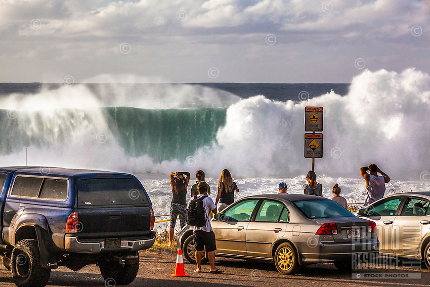 Spectators watch and take photos of giant waves during a large winter swell at Shark's Cove, North Shore, O'ahu.