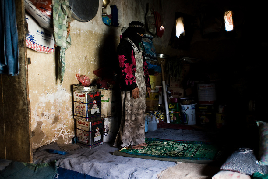 Yemen - Sana'a - Old jewish quarter in the outskirst of the capital. Most of the inhabitants of this area cannot afford to buy water so they walk 2 hours to reach the closest water well. Miryam 15 years old is  praying inside the house. Yemen's economy depends heavily on oil production, and its government receives the vast majority of its revenue from oil taxes. Yet analysts predict that the country's petroleum output, which has declined over the last seven years, will fall to zero by 2017. The government has done little to plan for its post-oil future. Yemen's population, already the poorest on the Arabian peninsula and with an unemployment rate of 35%, is expected to double by 2035..The trends will exacerbate large and growing environmental problems, including the exhaustion of Yemen's groundwater resources. Given that a full 90% of the country's water is used for agriculture, this trend portends disaster..Sanaa's well are expected to dry out by 2015, partly due to illegal drilling, partly because 40% of the city's water is diverted for qat production, and partly because conservation rules are difficult to enforce. Only 20% of the houses receive water, the other 80% has to collect it from pumps and wells. 15% of the urban population only uses bottled water as its primary drinking water source and that is why Yemen has one of the highest world mortality rate, most of the diseases being related to water..
