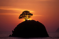 The sun sets behind one of many small limestone islets in Burma's Mergui Archipelago, High Rock.  High Rock, Mergui Archipelago, Burma/Myanmar, Andaman Sea