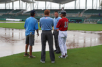 GCL Red Sox manager Tom Kotchman (11) talks with umpires Mark Bass and Grant Hinson as the infield is under water during a game against the GCL Rays on August 3, 2015 at the JetBlue Park at Fenway South in Fort Myers, Florida.  At left is a member of the Red Sox grounds crew;  the game was suspended after two innings due to the inclement weather.  (Mike Janes/Four Seam Images)