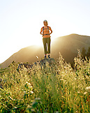 USA, California, young woman standing on rock in front of Mount Tamalpais