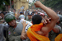 Riot policemen protect a man that was accused of trying to hit a Buddhist monk as other monk tries to punch him after an accident at a polling station in which voters protested against alleged election irregularities in Phnom Penh July 28, 2013. Cambodians voted on Sunday in an election likely to hand another five years in power to Asia's longest-serving prime minister, Hun Sen, but an energised opposition says there have been irregularities and it will continue to fight for true democracy.  REUTERS/Damir Sagolj (CAMBODIA)