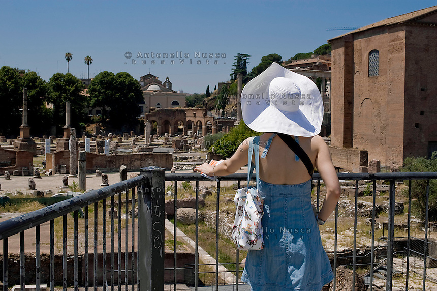 Rome continue to be one of the most visited city in the world..Roma continua ad essere una delle città più visitata al mondo.A turist at the Roman Forum.Turista al Foro Romano