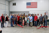 MEGAN DAVIS/MCDONALD COUNTY PRESS On Thursday, June 20, members of the McDonald County Chamber of Commerce gathered to celebrate as Daniel Cowin and family held a ribbon cutting for Daniel Cowin Construction in Pineville. The company provides roofing, siding, guttering, sheet metal and home repairs for the four-state area with a specialization in custom copper. The American flag pictured on the wall was hand-crafted in the Cowin Construction sheet metal shop.