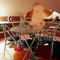 In a small dining area chrome chairs with multi-coloured seats surround a glass table on a colouful shag-pile rug