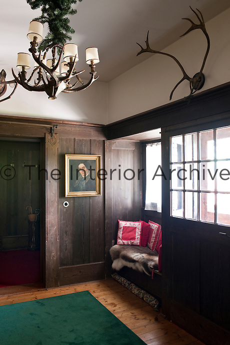 The cosy window seat is overlooked by a portrait painting in the wooden panelled living room