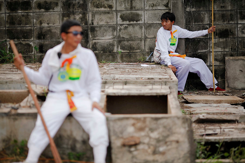 People rest after taking unclaimed human remains out of graves during a Thai Chinese ceremony at the Mang Teung Sua Jung Cemetery in Chonburi province southeast of Bangkok March 18, 2012. Every 10 years, hundreds of people wearing white, a customary colour for funerals and visiting temples, gather at this cemetery to exhume and cremate corpses as they believe they are helping the dead who have no friends or relatives. The ashes of the unclaimed bodies are spread on the sea to make room at the burial ground for more unclaimed bodies in the coming years. The tradition originated 90 years ago after diseases like Malaria killed many Thais of Chinese descent living in Chonburi.  REUTERS/Damir Sagolj (THAILAND)
