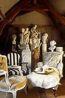 A collection of statues and busts are gathered behind a pair of chairs and a chaise-longue in an attic room