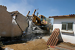 A bulldozer demolishes a house at the settlement of Netzer Hazani, in the Israeli settlement bloc of Gush Katif, Gaza Strip, two weeks after Israel evacuated some 8000 settlers from the conflicted strip.