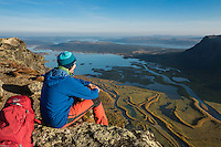 HIker enjoying view over Rapadalen from summit of Skierfe, Sarek National Park, Lapland, Sweden