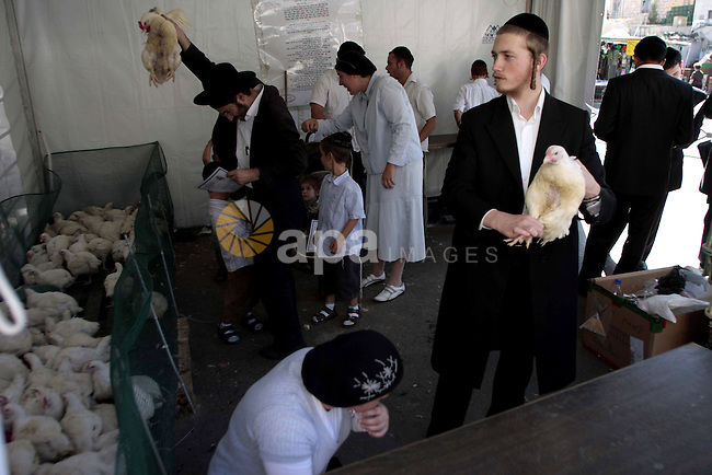 Ultra-Orthodox Jewish during watching as blood is drained from a slaughtered chicken during Kaparot in Jerusalem's Mea Shearim neighbourhood. Photo by Mohamar Awad