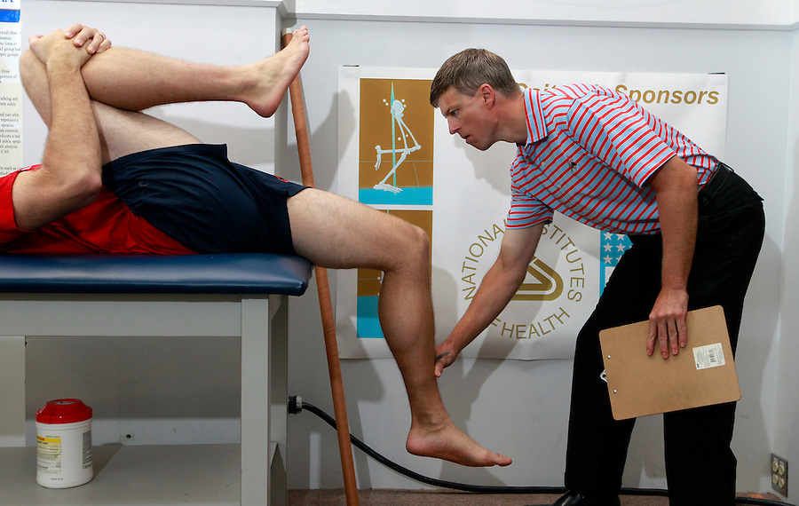 Director of the UVA SPEED Clinic Max Prokopy, left, shows Matt Clay a proper technique for stretching his leg muscles during a visit to the clinic in Charlottesville, VA. Photo/Andrew Shurtleff