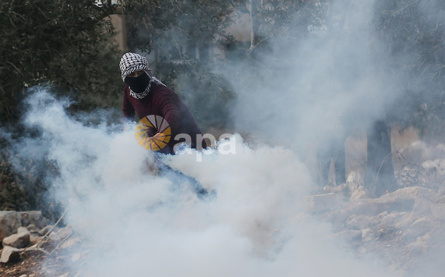A Palestinian protester returns throwing a tear gas canister during clashes following a weekly demonstration against the expropriation of Palestinian land by Israel in the village of Kfar Qaddum, near the West Bank city of Nablus on December 6, 2019. Photo by Shadi Jarar'ah