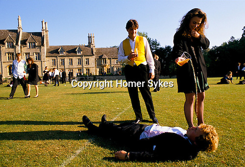 GGIRL POURING BEER ONTO HALF ASLEEP STUDENT, LYING, DRUNK, OUTSIDE ON THE GRASS PLAYING FIELD IN THE MORNING AFTER THE ROYAL AGRICULTURAL COLLEGE BALL, CIRENCESTER,