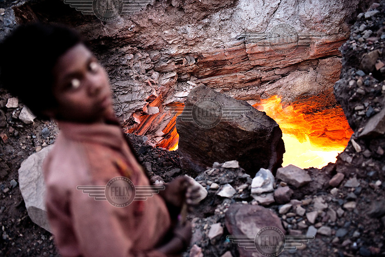A burning coal mine near the village of Bokapahari. Coal fires rage just below the surface of the ground, making it too hot to walk with naked feet. Noxious gases spew up from fissures, rendering the environment toxic. Residents who live above the furnace make $2 a day collecting small chunks of coal that they sell to illegal middlemen. One or two houses collapse annually into vast underground caverns left unfilled by abandoned mining operations.