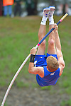 A male pole vaulter on his way over the bar.