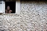A man looks out the window of his house in Mizak, a small village in the south of Haiti.