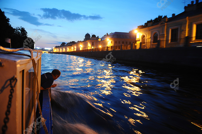 After midnight as a boat went down the Fontanka river towards the Neva a crewman on a boat leaned over the edge as the sky still remained bright during the city's White Nights, Russia, July 8, 2010