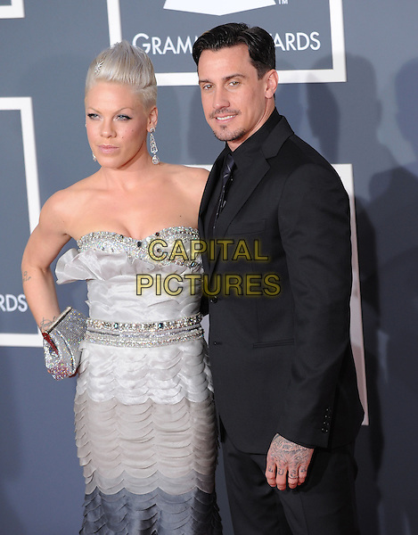 PINK (ALECIA MOORE) & CAREY HART.Arrivals at the 52nd Annual GRAMMY Awards held at The Staples Center in Los Angeles, California, USA..January 31st, 2010.grammys half length black grey gray strapless dress hand on hip piink pinnk beads beaded silver clutch bag dip dye dangling earrings suit married husband wife .CAP/RKE/DVS.©DVS/RockinExposures/Capital Pictures