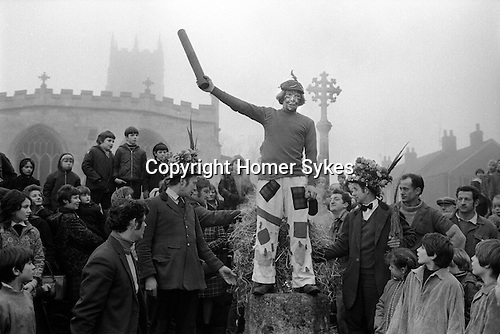 Haxey Hood Game. Haxey, Lincolnshire. Smoking the Fool. 1972.<br /> <br /> It is unclear how this rough version of rugby football began, it can only be traced with some certainty to an incident involving the first Lady de Mowbray who married John de Mowbray in 1298. One day when she was out riding her hood blew off and thirteen farm workers or &lsquo;Boggins&rsquo; in the vicinity gave chase to it. When it was finally rescued by the &lsquo;fool&rsquo; he was too shy to hand it over, so another Boggin (the &lsquo;Lord&rsquo;) gave it to her. Lady de Mowbray was so impressed with this gallantry that in her will she left a piece of land called the &lsquo;Hoodlands&rsquo; to the village as long as the inhabitants promised to re-enact the event annually. Consequently, each year on the 6 January the people not only of Haxey, but also of Westwoodside and other surrounding villages, do so. There are thirteen Boggins, the lord and the chief Boggin wear hunting pink, the fool the attire of a court jester.  After much singing of traditional songs in the village pubs, after lunch, they gather at the mounting stone by the village church where the fool makes a dash away from the crowd and the Boggins give chase until he is caught. They then carry him back to the stone where he tells the crowd the legend and the rules. <br /> <br /> They then make their way with the crowd to Upper Thorpe Field on the boundary of Westwoodside and Haxey There twelve sack hoods are thrown up. These are known as children's hoods. At about four o'clock a leather hood is thrown up, and a scrum known as the 'sway' forms round it. The teams of men, push against each other trying to get the hood to their favourite pub. Usually several hours pass before the hood reaches a goal, and when it does drinks are on the house. The hood stays in the pub until the following New Year's Eve when it<br /> is redeemed by the Boggins. <br /> <br /> Chief Boggin Arthur Clark &amp; the Fool Peter Bee about to be smoked, the
