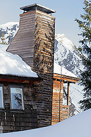 The chimney of the wooden-clad chalet against the distant snow-covered Alps
