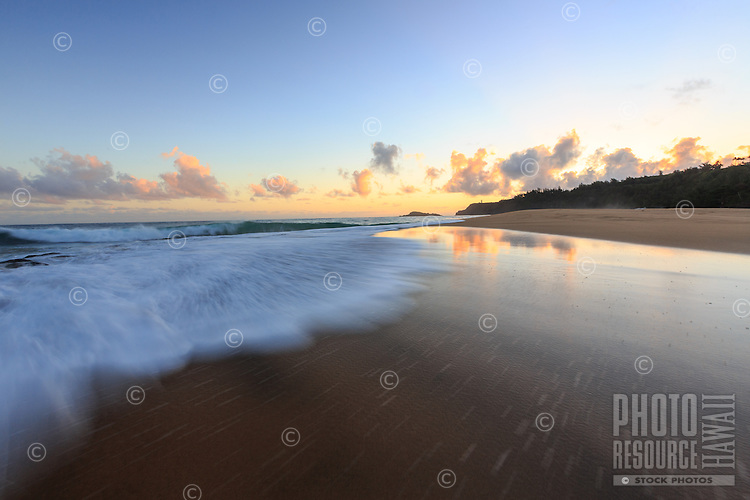 The surf rushes onto shore at dawn at Secrets Beach, Kaua'i.
