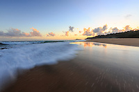 The surf rushes onto shore at dawn at Secrets Beach, Kaua'i.