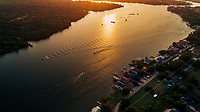 In this image, recreational boats criss-cross the majestic sun-drench waters of Lake LBJ as a beautiful golden sunset falls on Kingsland, Texas.