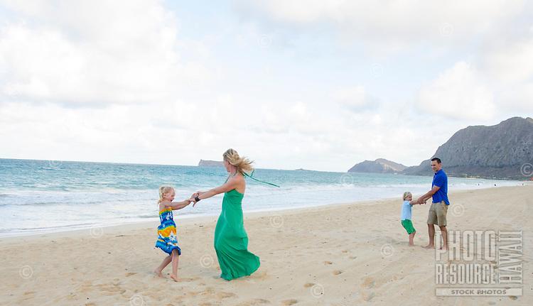 A family of four playing on Waimanalo Beach, O'ahu.