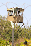 An Israeli soldier watches from a watchtower in the Israeli settlement of Karmei Zur during a non-violent demonstration in the West Bank village of Beit Ummar near Hebron on 10/07/2010.