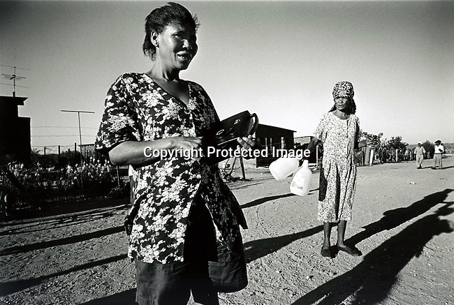 disiabu00030.Social Issues. Abuse. Elisabeth Lincoln, (Aka Poppy) the 35-year old grandmother of Baby Thsepang, walking along Sultana Road in the early morning on February 9, 2002 in Loisevale, Upington in South Africa. A female friend has just bought two jugs of wine and a bottle of brandy. Baby Thsepang was raped in October-2001 in Loisevale It is a poor and destitute colored/black township where unemployment is very high and a high number of abuse and alcohol cases..©Per-Anders Pettersson/iAfrika Photos