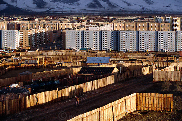 The Soviet-style apartment blocks on the edge of Ulaanbaatar, a legacy of Mongolia's Communist past, are now surrounded by squatters; more accurately, urban homesteaders. Former nomads, they have precisely parceled out the land and staked out their neat gers. The gers lack indoor plumbing, but in other ways are more comfortable than the city's crowded apartments. Hungry Planet: What the World Eats (p. 228). This image is featured alongside the Batsuuri family images in Hungry Planet: What the World Eats.