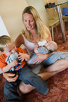A woman sits crosslegged at home on the carpet of her living room floor breastfeeding her baby  whilst cuddling her older boy in her lap at the same time.  <br /> <br /> 09/07/2011<br /> Hampshire, England, UK