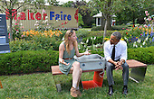 """United States President Barack Obama (L) listens to Sandra Richter of Cambridge, Massachusetts, as they sit on an example of eco-friendly urban furniture, a solar-powered sofa, or """"soofa"""", which can be used to charge electronic items, at the White House Maker Faire in the Rose Garden, June 18, 2014, in Washington, DC. The Faire is a series of projects by students,  entrepreneurs and regular citizens using new technologies and tools to launch new businesses and learning new skills in science, technology, engineering and mathematics. <br /> Credit: Mike Theiler / Pool via CNP"""