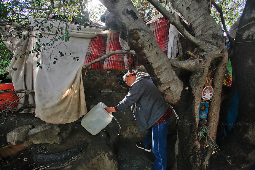 A man originally from the state of Sinaloa washes his face in a makeshift refuge in a canyon overlooking the fence that separates Mexico from the United States. The 44-year-old man, who declined to give his name, has lived in the United States for over a decade and was deported in early November of 2012 after his place of employment was raided by immigration officers. He was deported to the state of Tamaulipas. He has tried to return to his home and family in East Los Angeles 14 times since late November but has been caught by the border patrol. He now lives in this makeshift tent and hopes to return to his family in the near future. He works as a day laborer and a carpenter in the city of Tecate  whenever he is able to find work. He used to be a carpenter in Los Angeles...Tecate, Baja California, Mexico - February 8, 2013.  (Javier Manzano / For The Washington Post).