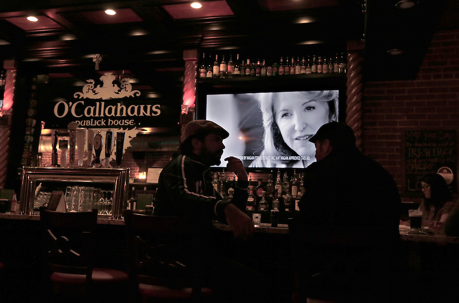 MOCKSVILLE, NC - NOVEMBER 2:  A television advertisement in support of North Carolina Democratic incumbent for U.S. Senate Kay Hagan plays while patrons chat at O' Callahans restaurant in Mocksville, NC, on Sunday, November 2, 2014.  (Photo by Ted Richardson/For The Washington Post)