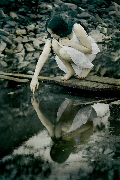 a woman with long black curly hair in white dress squating to the water and touching her water reflection with one finger