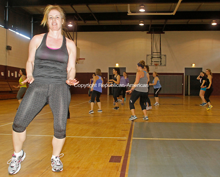 Torrington, CT-19 April 041914MK01 Jess Huttig leads a Zumba class attended by people who made donations for injured Torrington native Alita Perez at St. Peter/St. Francis School Gym in Torrington on Saturday morning.  Julie Fabiaschi event coordinator said about 25 people participated in the Zumba class along with the yoga session that followed and many donors who contributed but did not stay for the event. Perez was on vacation in Vietnam when she was struck by a motor bike and broke her leg. She developed an infection which has made healing difficult. Michael Kabelka / Republican-American
